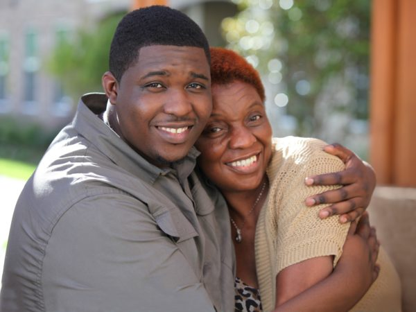 African American man hugging his mom and smiling