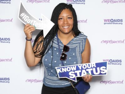 "Woman holding an #IGotTested and a ""Know Your Status"" signs"
