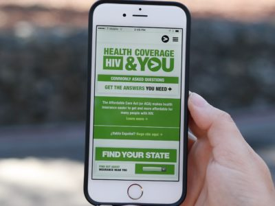 Hand holding smartphone displaying Greater Than AIDS Health Coverage, HIV and You campaign website