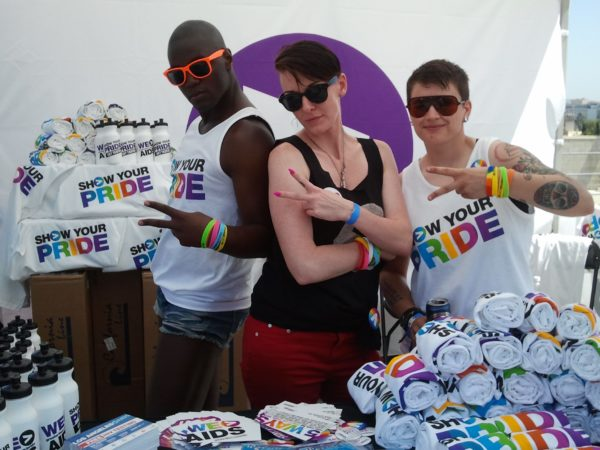 Three people making the greater than sign with their hands at the Speak Out Pride event