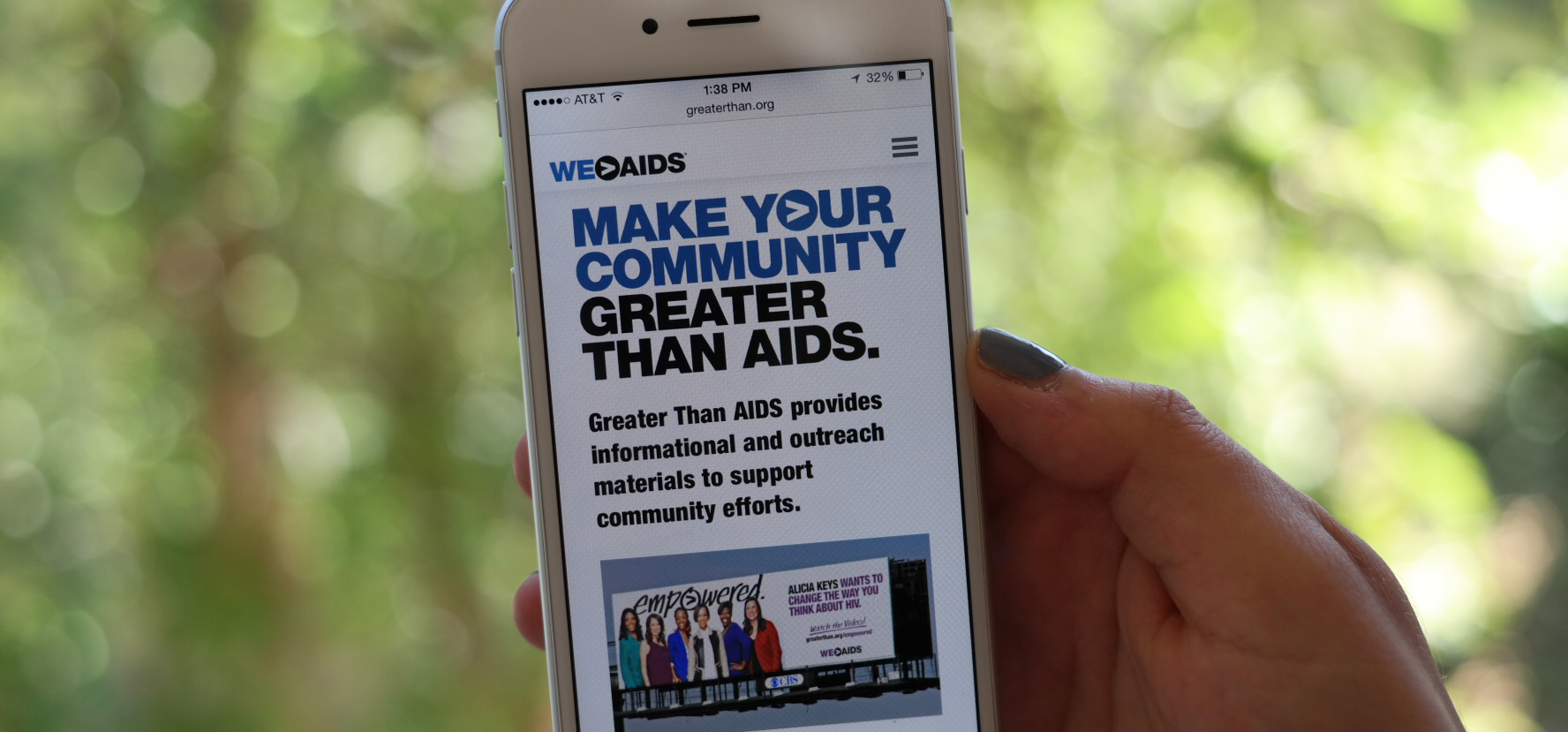"Hand holding a smartphone displaying a graphic reading ""Make your community Greater Than AIDS"""