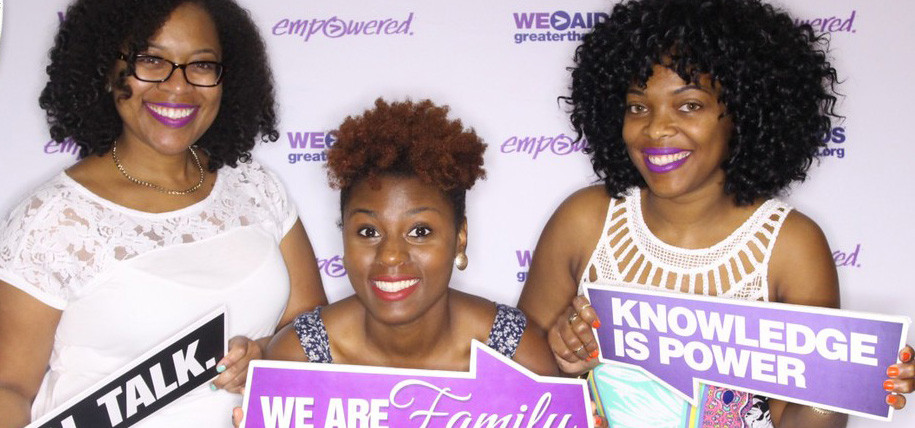 "Three women holding signs reading ""Knowledge Is Power"" and ""We Are Family"" at EssenceFest Booth"