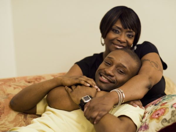 Black man and black woman holding each other smiling