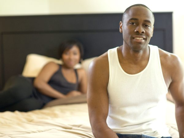 Man sitting on the edge of the bed with a woman in the background