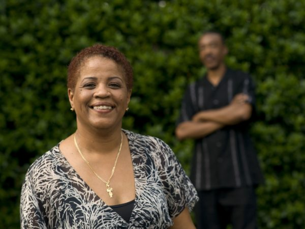 Woman smiling with a man in the background