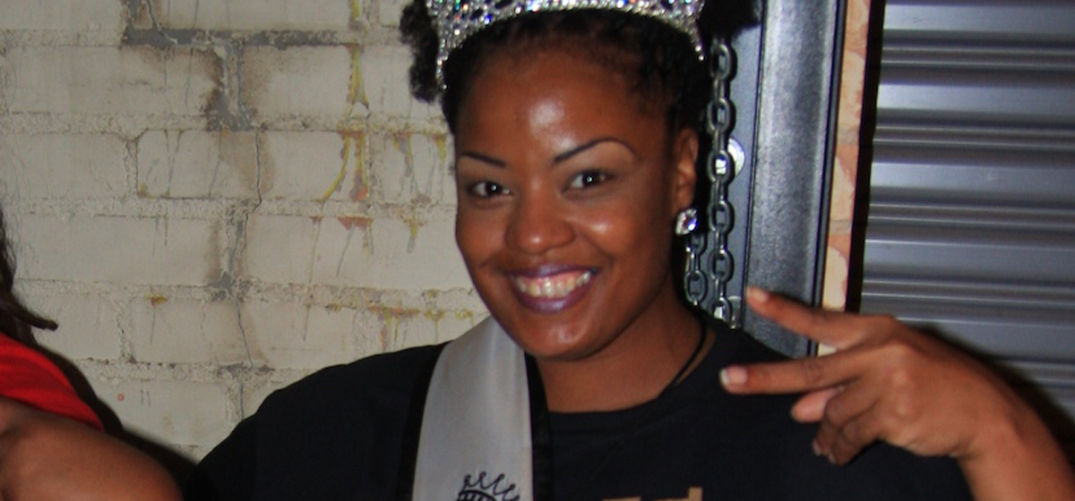 Black woman smiling while making the greater than sign with her fingers