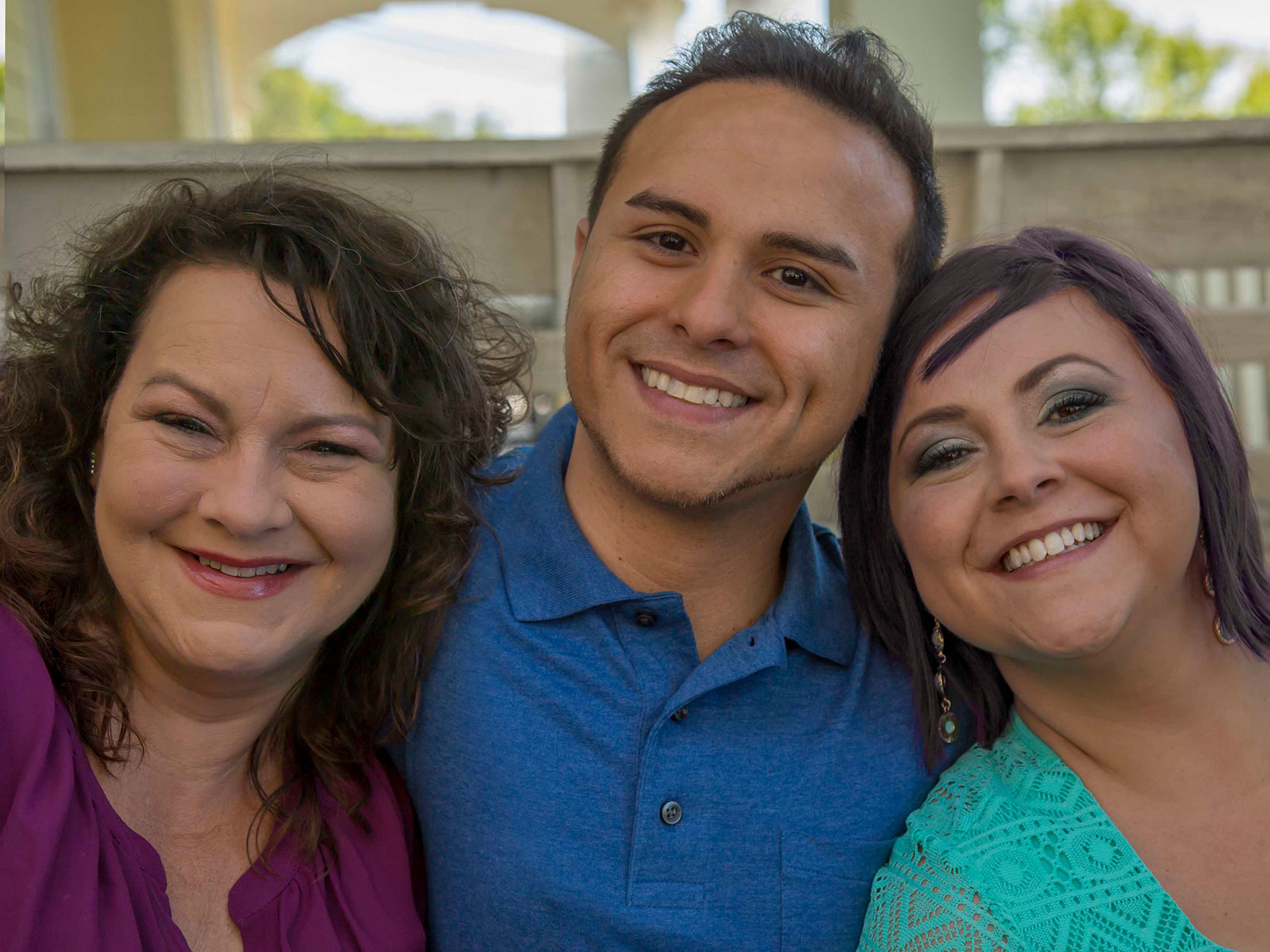 Young man smiling with his mom and sister