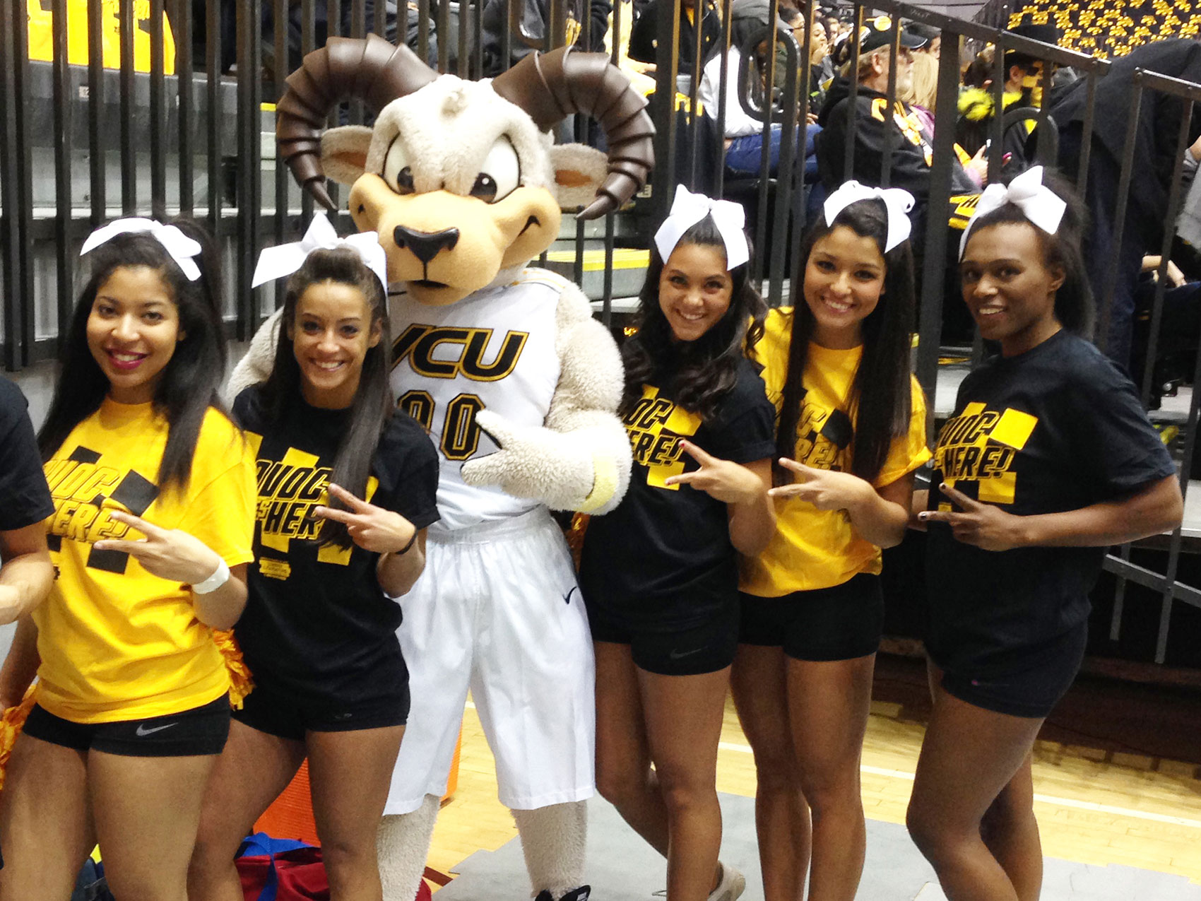 Cheer squad posing with mascott making greater than symbol with their hands