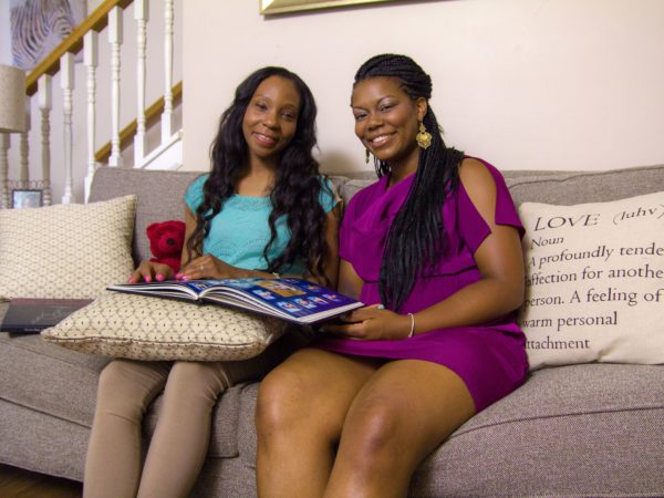Two African American women sitting on a couch looking at a yearbook