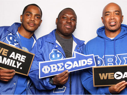 Three black men holding up Greater Than AIDS signs