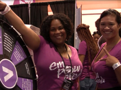 Volunteers Trina and Amy wearing magenta Empowered shirts at Greater Than AIDS event