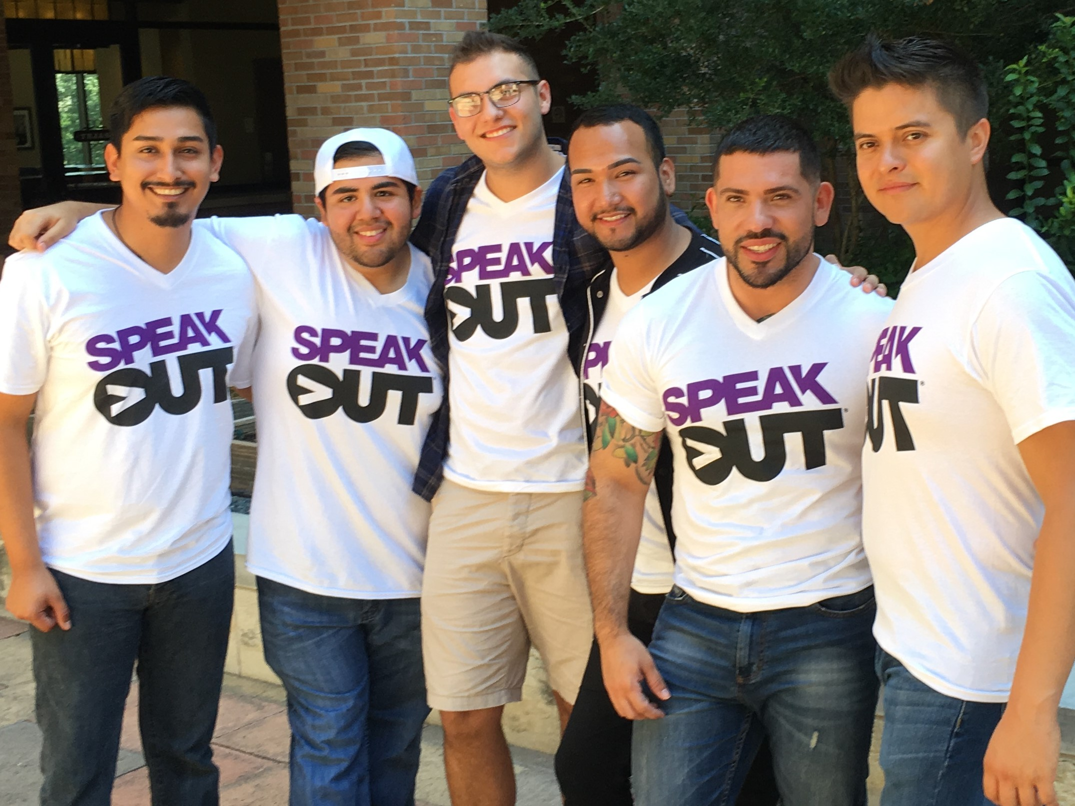 Group of people standing wearing Speak Out white t-shirts