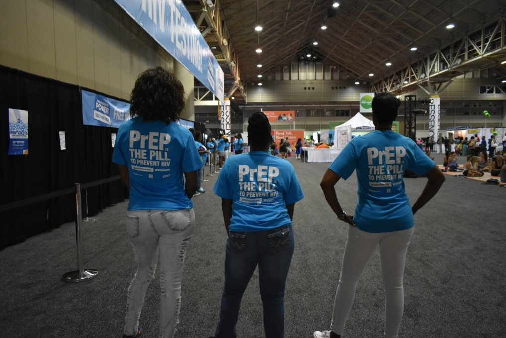 "Three women with GTA-branded shirts with the text ""PrEP THE PILL TO PREVENT HIV"" at ESSENCE Fest 2018"