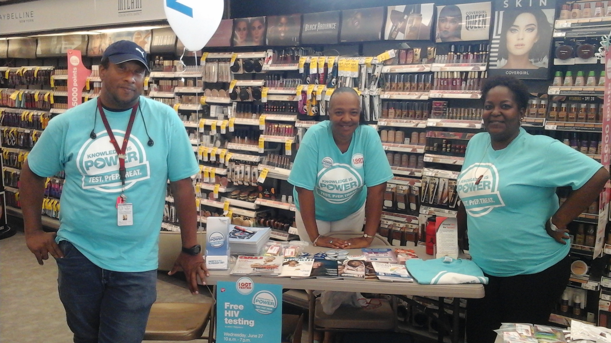 People standing at HIV information table at Walgreens