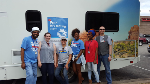 People standing in front of HIV testing trailer