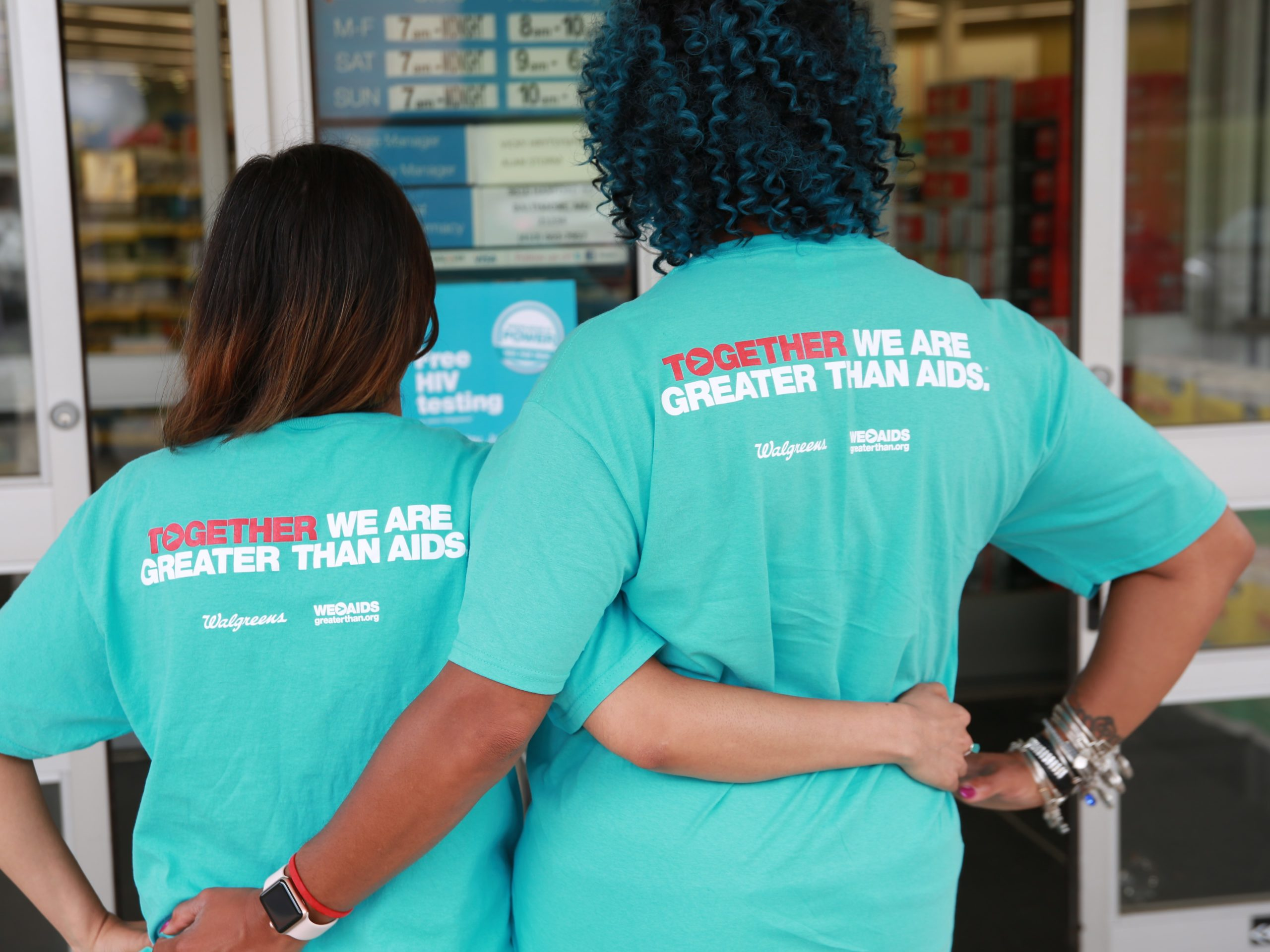 Two women in Greater Than AIDS shirts