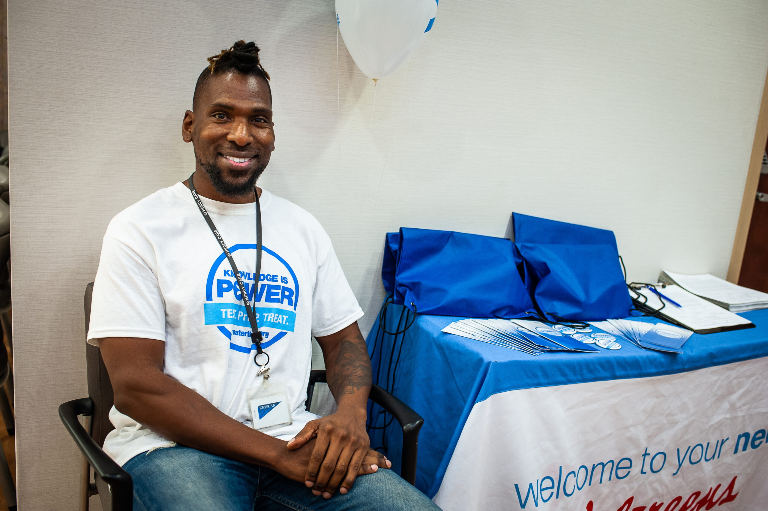 Man smiling at a table at national HIV testing day location