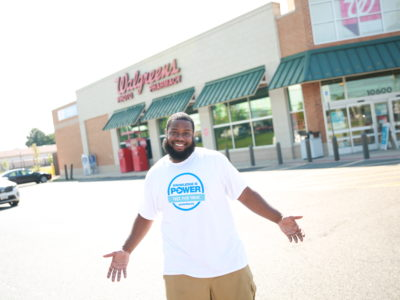 Man smiling in Greater Than AIDS t-shirt in front of Walgreens